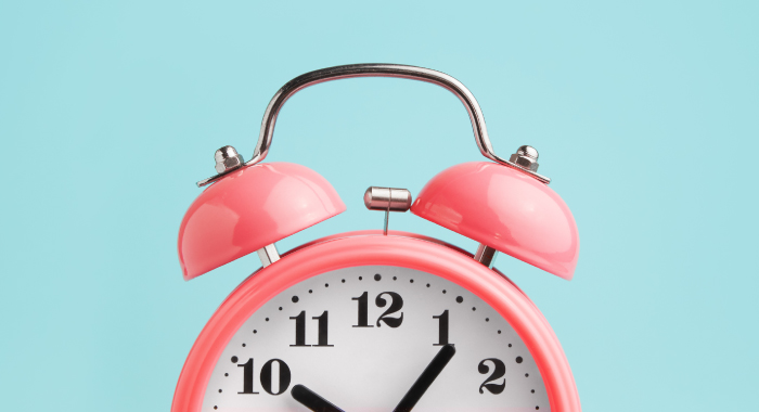 pink alarm clock on a blue background