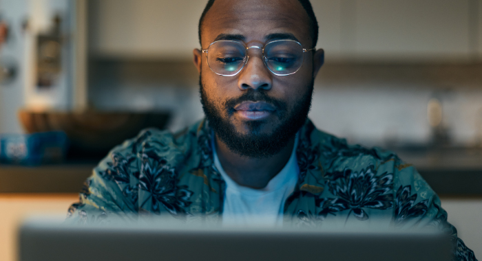 Man sitting, looking at a laptop