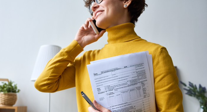 Person on the phone while holding tax documents