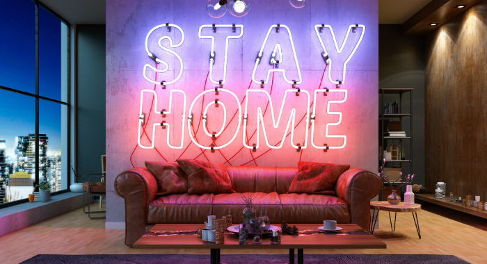 "A couch with a neon sign behind it that says, ""Stay Home."""