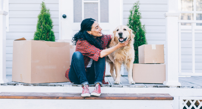 Woman sitting outside with her dog surrounded by moving boxes