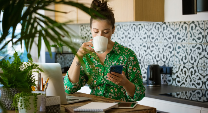 Woman sipping coffee and looking at her phone