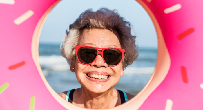 elderly person looking through a donut shaped swim float