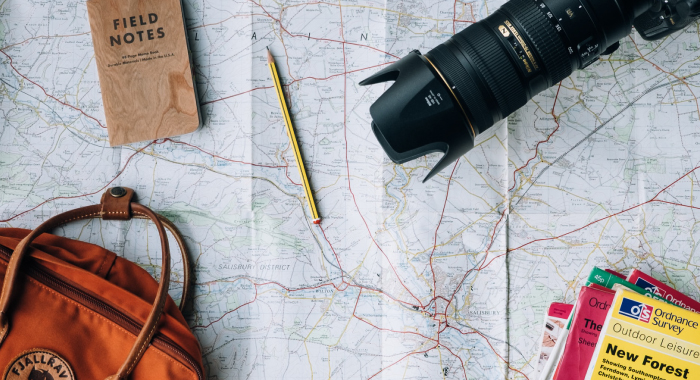 A camera, a bag, a notebook, a pen, and other items sitting on top of a map.