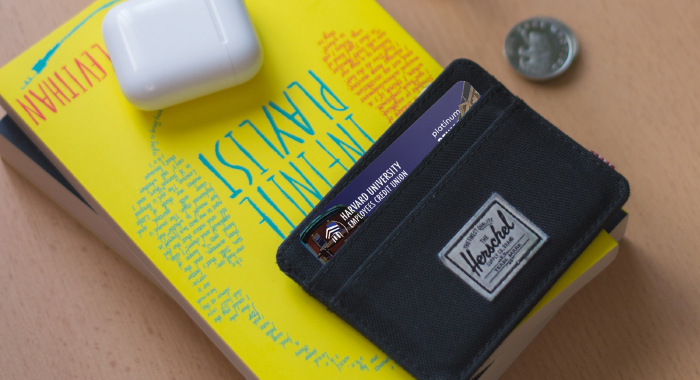 Wallet with an HUECU credit card in it, sitting on top of a book