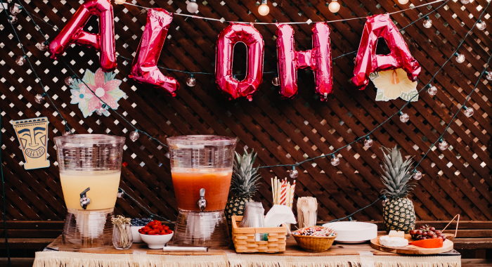 Aloha balloon sign hanging over a table with pitchers of drinks.