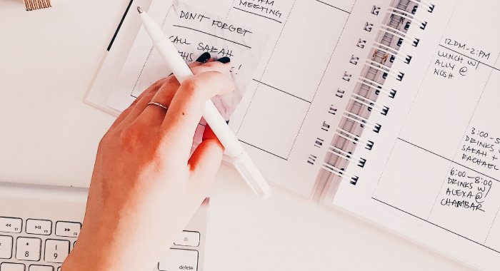Person with a pen in hand looking at a planner