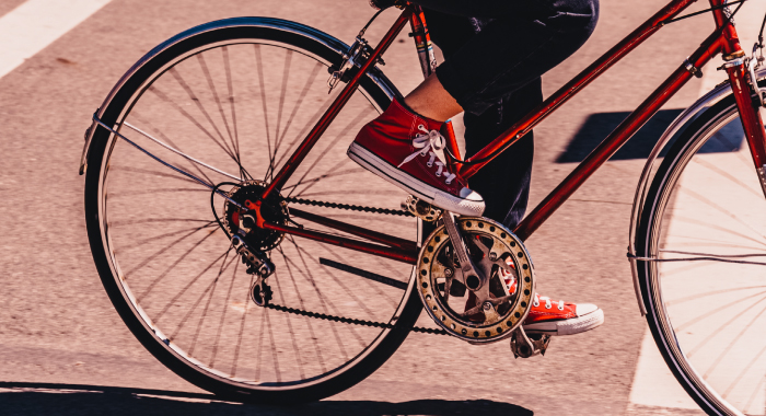 person in red converse shoes pedaling a bike