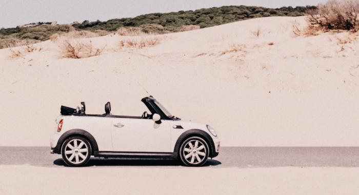 A tan mini cooper driving along the sand
