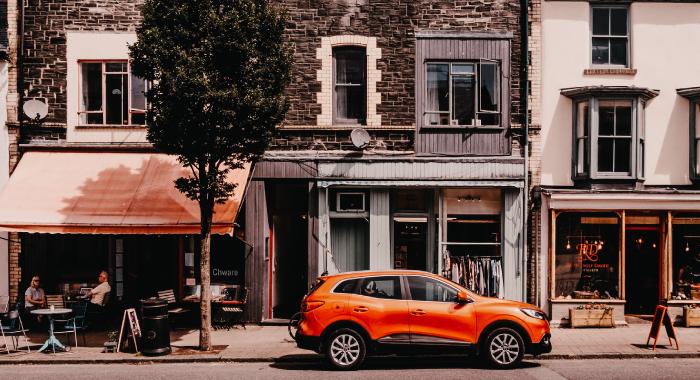 orange car parked outside a building