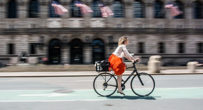 Woman riding a bike in front of the Boston Public Library