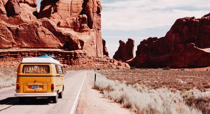 old van driving down a road along a canyon