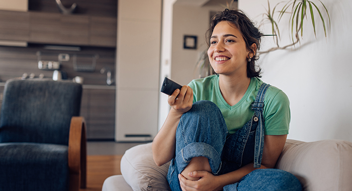young person smiling and holding a remote control while sitting on a couch