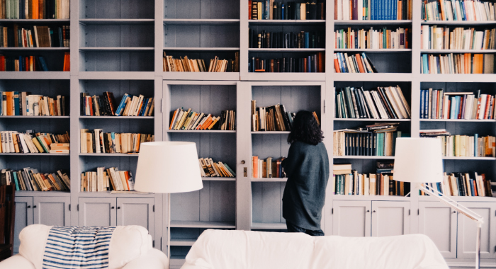person looking at a large bookcase