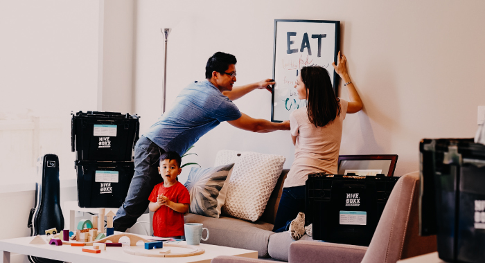 A family of three hanging a piece of artwork in their home