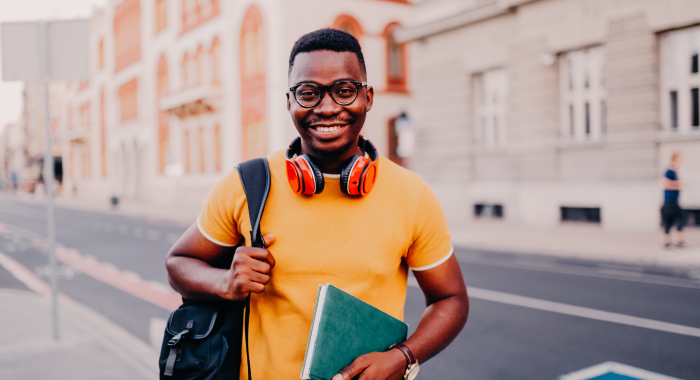 person with a backpack, notebook, and headphones smiling at the camera
