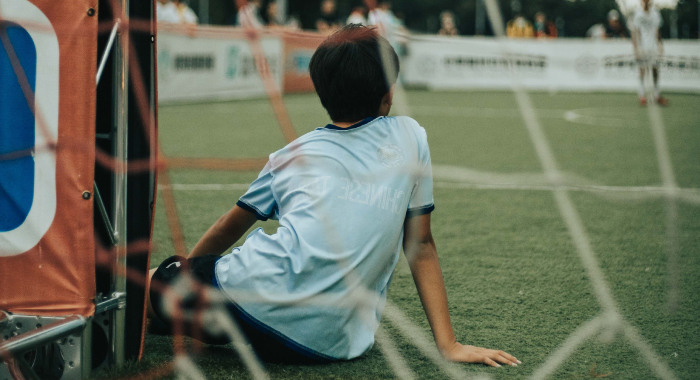 Child sitting on turf in front of a goal net