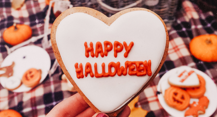 """heart-shaped cookie with """"Happy Halloween"""" written in orange icing"""
