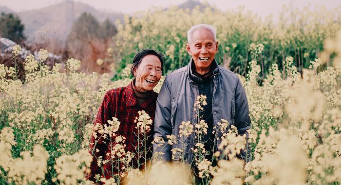 An elderly couple posing in a field