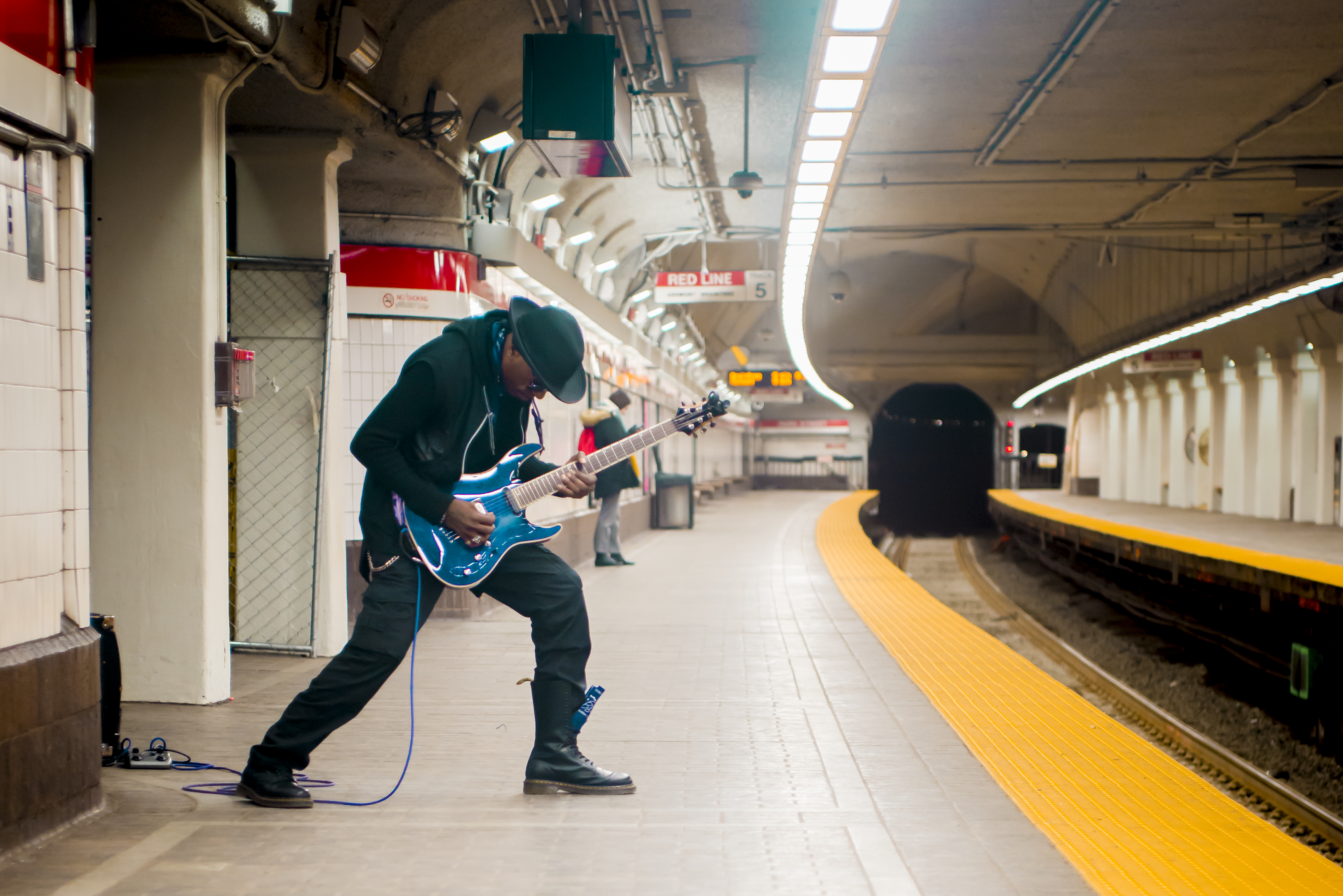 Man playing the guitar at a T stop