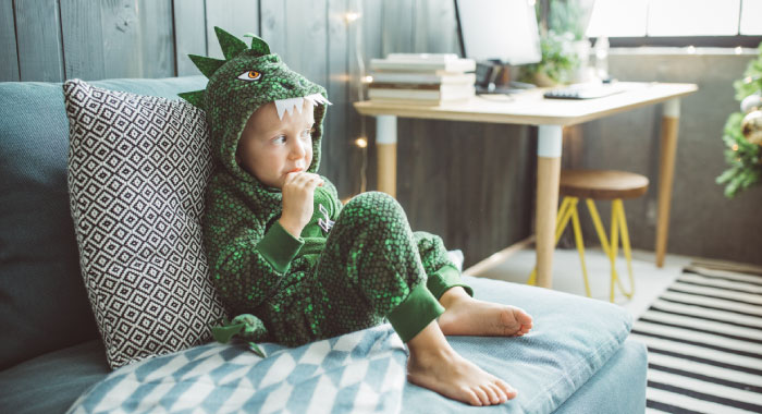 child with a dinosaur costume sitting on a bed