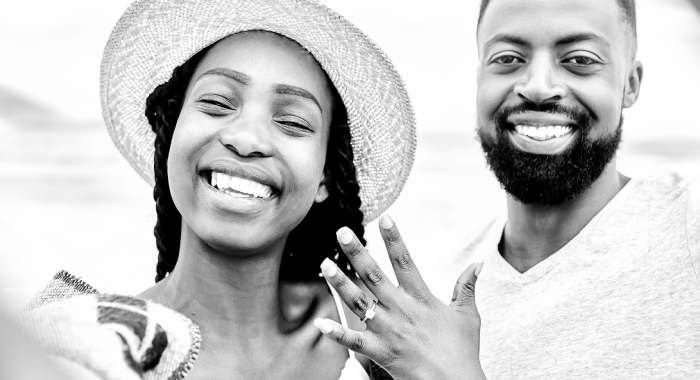 Happy couple showing engagement ring