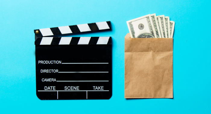 clap board and bag of money on a blue background