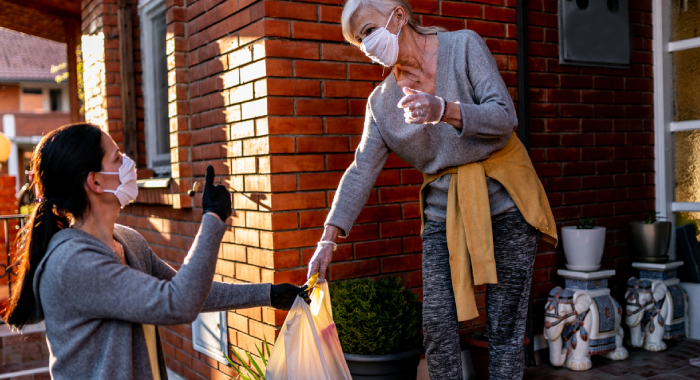 two women wearing face masks and gloves exchange a grocery bag.