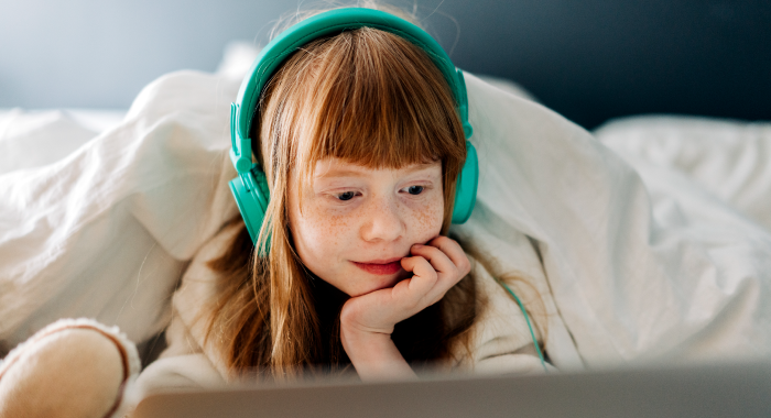 Young girl with headphones on watching something on the computer